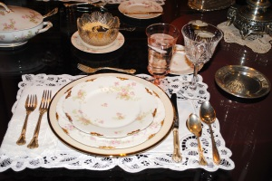 Place setting of Limoges with Chantilly silver by Gorham and Cherrywood crystal also by Gorham on Battenburg lace placemats.